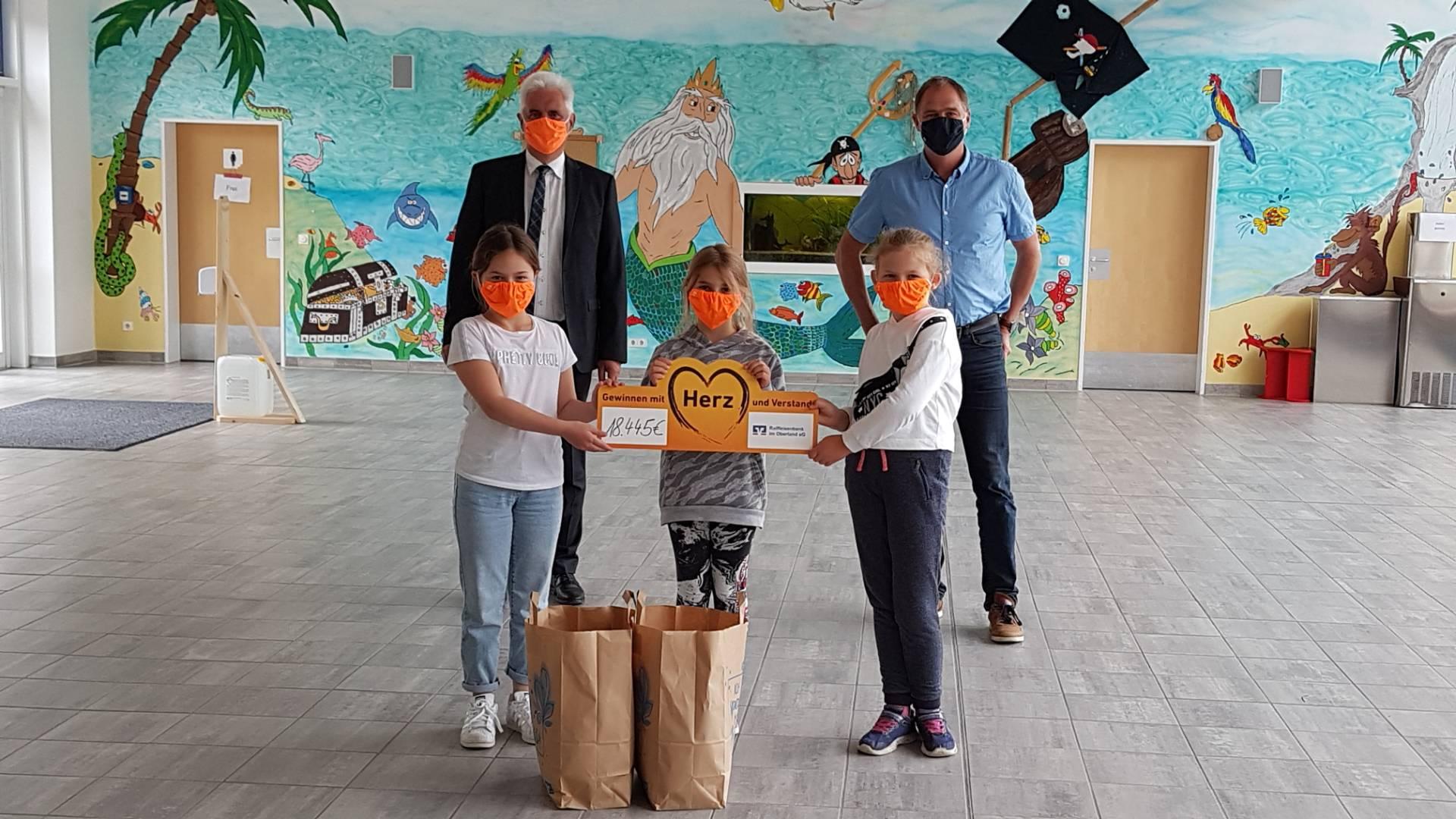 Der Schulrektor der Grund- und Mittelschule, Markus Rewitzer, und drei seiner Schülerinnen freuten sich über die neuen Masken. Überreicht wurden sie vom Vorstandsvorsitzenden der Raiffeisenbank im Oberland eG, Hansjörg Hegele.