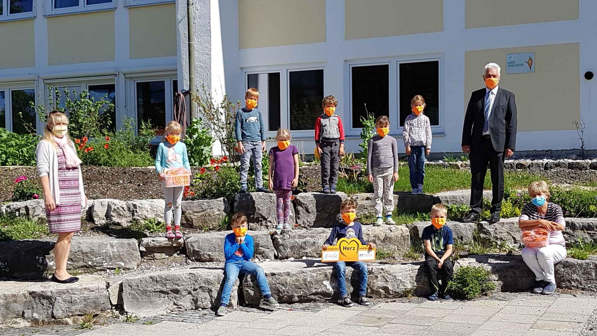 Die Rektorin der Grundschule, Heidi Dodenhöft, und die Schülerinnen und Schüler der Klasse 1 a mit ihrer Lehrerin Birgitt Kohl freuten sich über die neuen Masken.